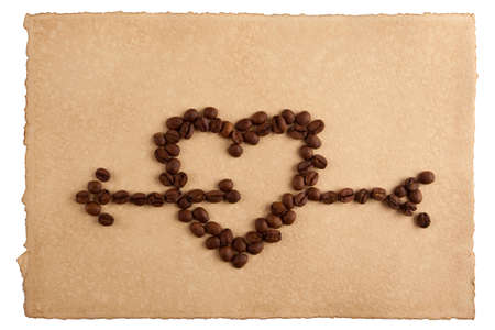 Heart symbol made from coffee crops on hand-made paper and isolated on white  Place for text  photo