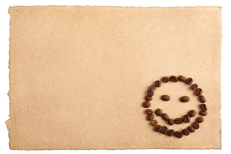 Childish smiley face symbol made from coffee crops on hand-made paper and isolated on white  Place for text  photo