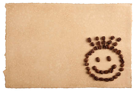 Childish smiley face symbol made from coffee crops on hand-made paper and isolated on white. Place for text. photo