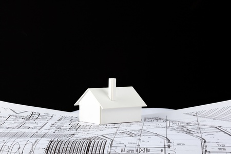 Small simple white model house on architectural prints and black background for copyspace