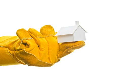 Worker s hand in a safety glove holding a model house on his index finger, isolated on white  photo