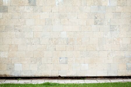 Abstract urban wall with grass and a sidewalk photo