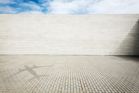 Urban grungy street wall with a shadow on the ground  of a plane flying by, may be used as background or texture photo