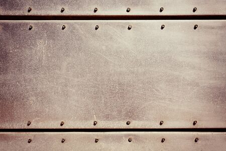 Old grungy, dirty and scratched metal plate with screws Stock Photo