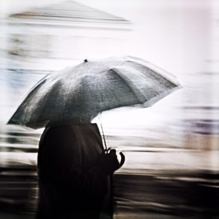cold weather: Man in a rain walking with umbrella. Unrecognizable person in motion blur.