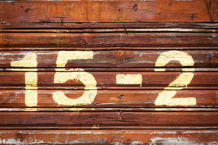 House number, sprayed on painted wooden wall photo