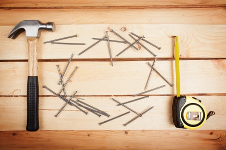 home repair: Wood background with a hammer, ruler and some nails, home improvement concept Stock Photo