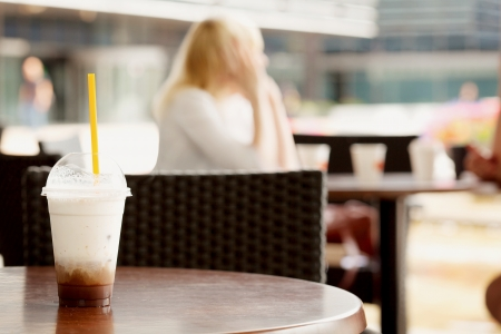 Glass of ice coffee on a table at a cafe with unrecognizable girl out of focus in the background Stock Photo