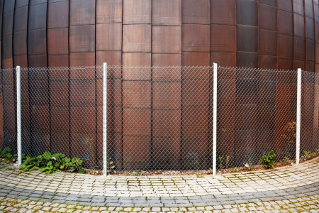 Copper round urban wall with a fence around it Stock Photo