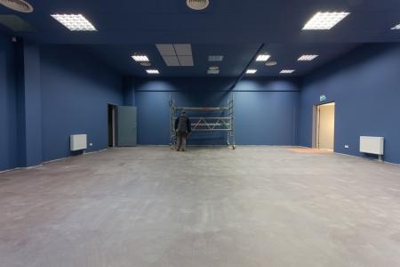 Unfinished building interior, blue hall. Unrecognizable worker Standard-Bild