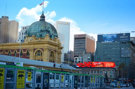 flinders: View of the busy Flinders Street with communters and transport, Flinders Street Railway Station and modern buildings in Melbourne.