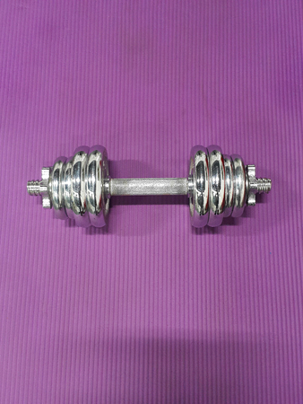 Top veiw chrome metal frame coated dumbells isolated on purple
