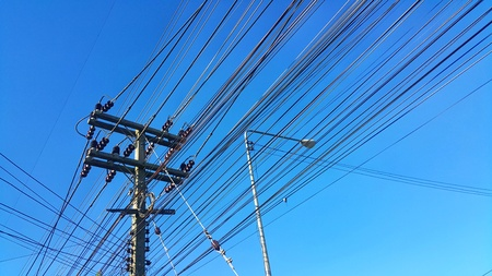 High voltage tower and power cable with blue sky background