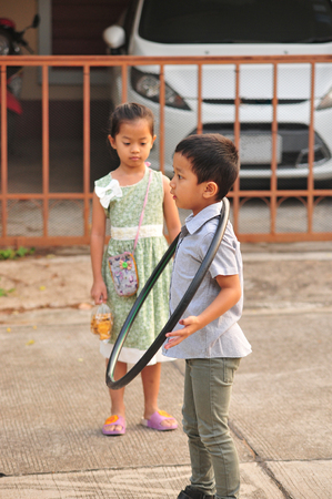 Boy and girl playing hoop on the street in town