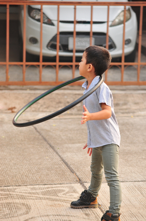 Boy and girl playing  hoop on the street in town Imagens