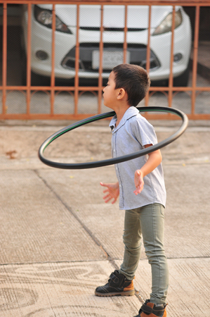 Boy  playing hoop on the street in town Imagens