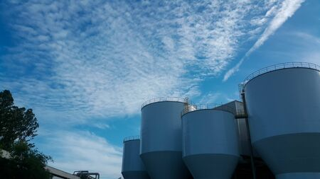 Beautiful blue sky with cloud over material raw tank in factory 版權商用圖片