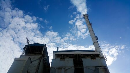 Beautiful blue sky with cloud over smokestack of power poiler in factory