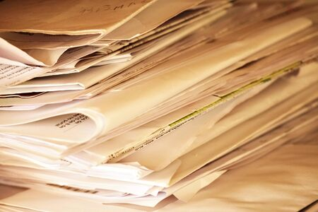 Piles of unfinished paper files on work desk office