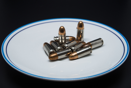 Bullets in a plate on the served table isolated on black background