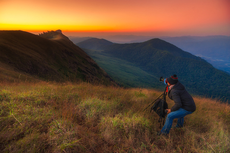 Nature photographer framing a shot, taking pictures at sunrise in the mountains.At doi-Monjong Chiangmai Thailand Stock Photo