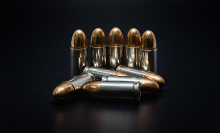 9mm ammo: 9mm silver bullet for a gun on drak background.Bullet isolated