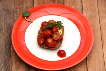 Tomatoes on toast, presented on a red and white plate Stock Photo