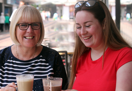Mother and grown up daughter, enjoying coffee in the sun