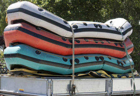 Inflatable rafts stacked on a cars trailer.