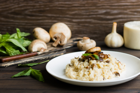 Risotto with mushrooms on a dark wooden background