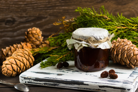 A jar of homemade jam made of pine cones on a dark background