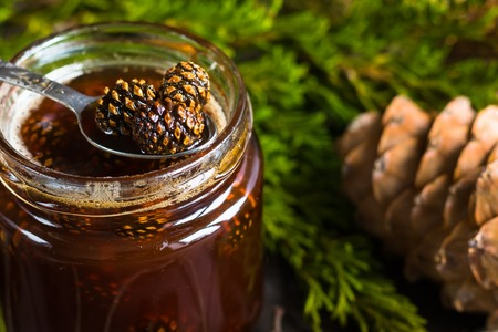 A jar of homemade jam made of pine cones on a dark background