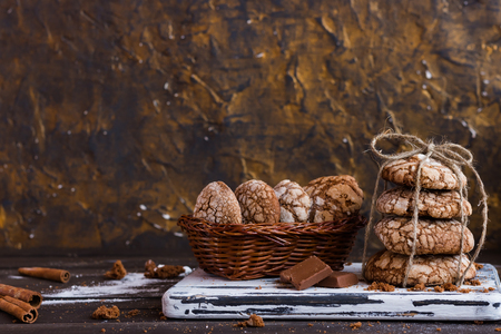 Chocolate biscuits with cracks on a dark wooden background