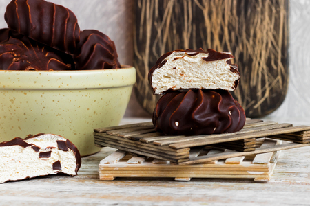Marshmallow in chocolate on a wooden background