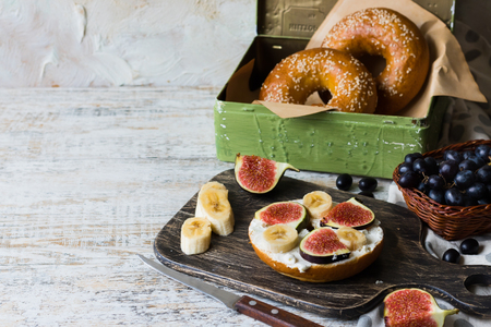 Bagels with fig and banana on curd cheese for breakfast