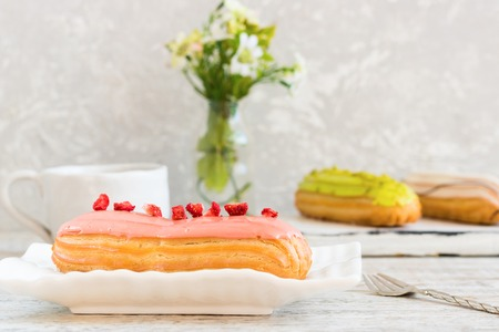 Pistachio, vanilla, strawberry eclair in glaze Stock Photo