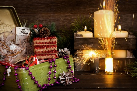 Box with Christmas toys on a background of candles and Begalsky lights