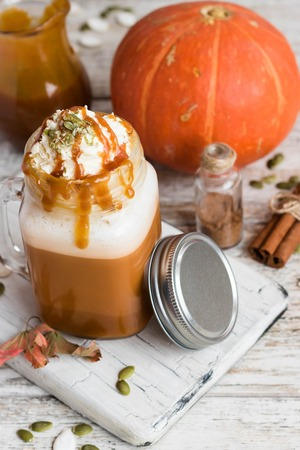 Spicy pumpkin latte with spices and a cap of whipped cream decorated with salted caramel and crushed pumpkin seeds