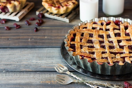 Traditional American cherry pie and mini pies on a dark wooden background