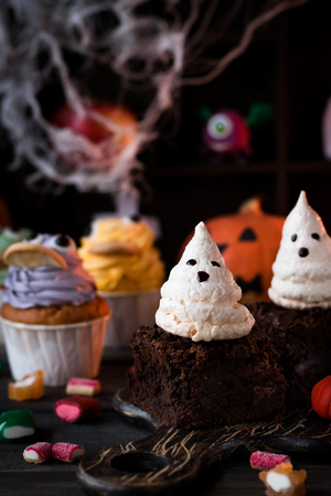 Dessert for Halloween chocolate brownies with ghosts of meringues