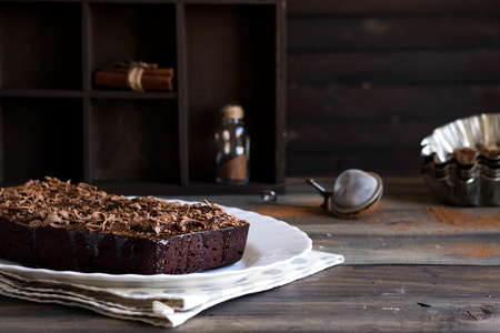 Chocolate pound cake with chocolate icing and chocolate chips on wooden background