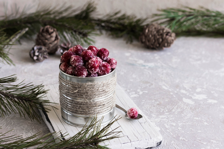 Candied cranberries in a tin rustic bank on the background of fir branches Imagens