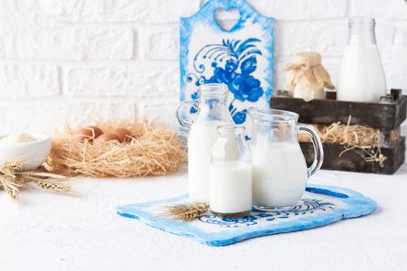 Bottles of milk of various shapes and sizes on a light background