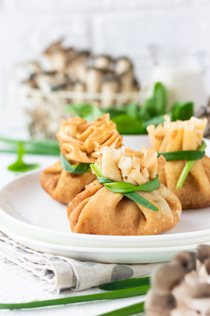 Pancakes rolled into a bag and stuffed with fried oyster mushrooms with spinach