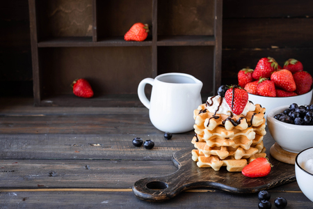 Viennese waffles with whipped cream and fresh berries as a summer breakfast concept