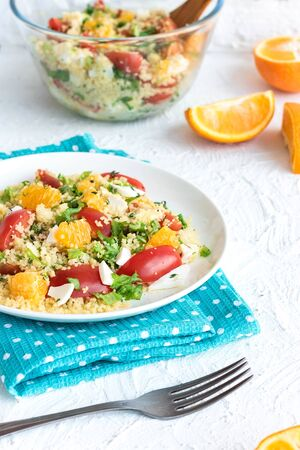 Healthy and simple food, light summer lunch, fragrant salad with couscous and oranges on a light background