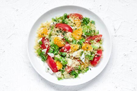 Comida sana y sencilla, almuerzo ligero de verano, ensalada aromática con cuscús y naranjas sobre un fondo claro