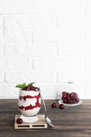 Light berry dessert. Trifle red velvet with cherry and cream cheese