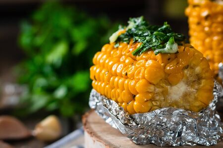 Baked corn with spiced butter on a rustic wooden background. Food for the holidays and barbecue. Autumn harvest.