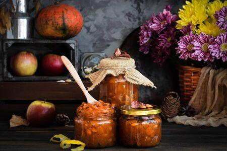 Marmellata di zucca su un fondo rustico scuro. Raccolto autunnale. Natura morta autunnale accogliente. Preparazioni fatte in casa per l'inverno.